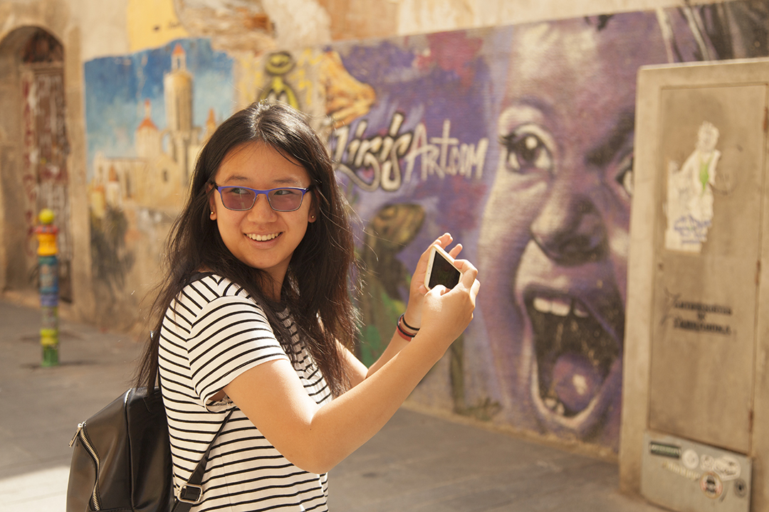 Female student taking selfie in front of street art