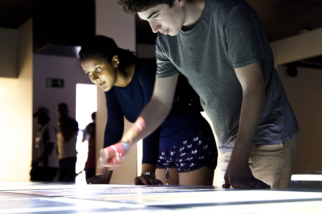 Female and male student pouring over iluminated photoboard