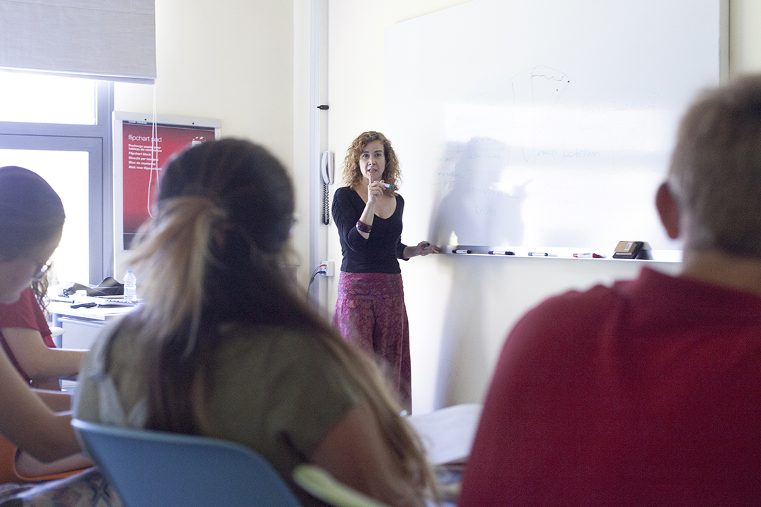 Female teacher at whiteboard facing three students