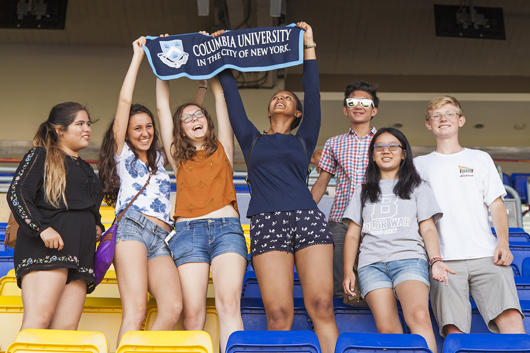 Students at stadium raising Columbia University banner